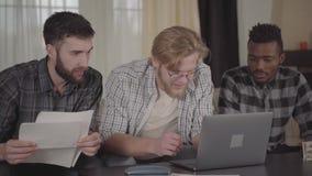 Dos caucásicos y hombres afroamericanos uno que descansan junto en casa, sentándose delante del ordenador portátil Compañía  metrajes