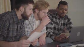 Dos caucásicos y hombres afroamericanos uno que descansan junto en casa, sentándose delante del ordenador portátil Compañía  almacen de video