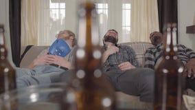 Dos caucásicos y hombres afroamericanos uno que duermen en el sofá después de mirar el boxeo en la TV Botellas de cerveza vac almacen de video