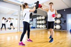 Dos centraron el boxeo de entrenamiento de la gente en el gimnasio de la aptitud Imágenes de archivo libres de regalías