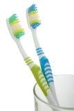 Dos cepillos de dientes en vidrio Imágenes de archivo libres de regalías