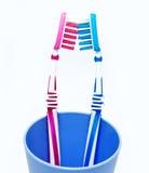 Dos cepillos de dientes en vidrio en blanco Imagenes de archivo