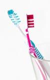 Dos cepillos de dientes en vidrio en el fondo blanco Fotografía de archivo libre de regalías