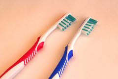 Dos cepillos de dientes higiénicos rojos y azules en fondo coloreado fotografía de archivo