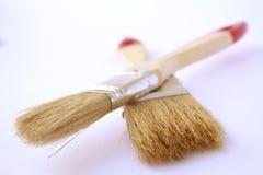 Dos cepillos de pintura con las manetas del rojo en un documento sobre una diagonal Foto de archivo libre de regalías