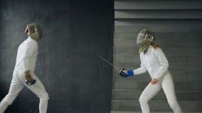 Dos cercadores hombre y mujer sacuden las manos en el extremo de la competencia de cercado dentro almacen de metraje de vídeo