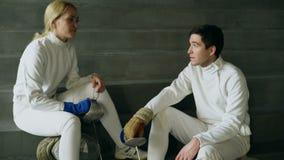 Dos cercadores jovenes hombre y mujer que hablan después de cercar el entrenamiento dentro