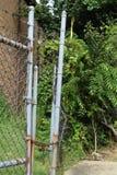 Dos cercas del alambre de púas con la cadena y la cerradura aherrumbrada Fotografía de archivo