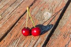 Dos cerezas en una tabla de madera Fotografía de archivo libre de regalías