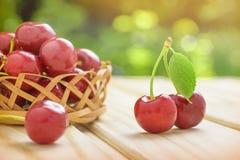 Dos cerezas rojas maduras con una hoja verde Una pequeña cesta por completo de cerezas Verde claro borroso fondo Día asoleado fotos de archivo libres de regalías