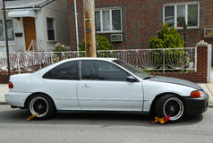 Dos cerraduras de rueda en un coche ilegal parqueado en Brooklyn, NY Imagen de archivo libre de regalías