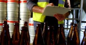 Dos cerveceros que comprueban las botellas de cerveza 4k almacen de video