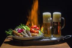 Dos cervezas y salchichas con la llama en fondo imagen de archivo libre de regalías