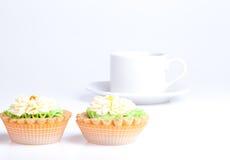 Dos cestas de la torta en una tabla con la taza blanca Imagenes de archivo