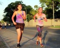 Dos Chearful que funciona con a las muchachas adolescentes cubiertas con la pintura del polvo Foto de archivo