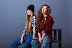 dos chicas jvenes atractivas hermosas en sentarse de los vaqueros fotografa de archivo