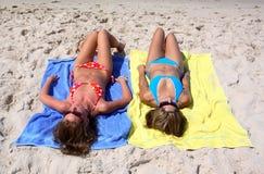 Dos chicas jóvenes atractivas que ponen en una playa asoleada en vacaciones u holi Foto de archivo libre de regalías