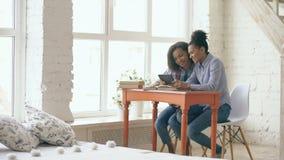 Dos chicas jóvenes cabelludas rizadas atractivas de la raza mixta que se sientan en la tabla se divierten mientras que aprenden l almacen de metraje de vídeo