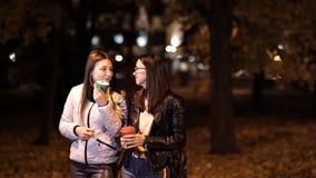 Dos chicas jóvenes caminan a través de las calles de una ciudad desconocida en un café de la tarde y de la bebida del otoño almacen de video