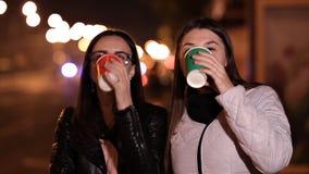 Dos chicas jóvenes caminan a través de las calles de una ciudad desconocida en un café de la tarde y de la bebida del otoño metrajes