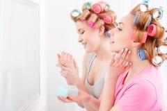 Dos chicas jóvenes cerca del espejo fotos de archivo