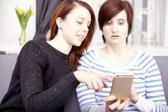 Dos chicas jóvenes con el teléfono elegante Imagenes de archivo