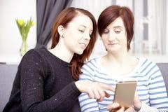 Dos chicas jóvenes con el teléfono elegante Imagen de archivo libre de regalías