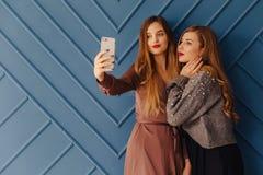 Dos chicas jóvenes elegantes atractivas con el teléfono en fondo simple de la aguamarina imagen de archivo