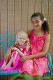 Dos chicas jóvenes en color de rosa en banco azul Fotos de archivo