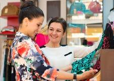Dos chicas jóvenes en el boutique que elige el vestido Fotografía de archivo