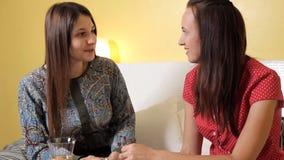 Dos chicas jóvenes en la igualación en casa del champán de consumición, la sonrisa y hablar Hogar de la tarde, calor, comodidad metrajes