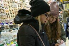 Dos chicas jóvenes en la tienda de regalos eligen recuerdos imagenes de archivo