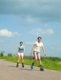 Dos chicas jóvenes en las láminas del rodillo Imagen de archivo libre de regalías