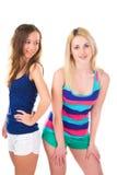 Dos chicas jóvenes en pantalones cortos en el fondo blanco Fotos de archivo libres de regalías