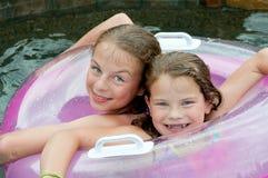 Dos chicas jóvenes en piscina con el flotador Fotografía de archivo