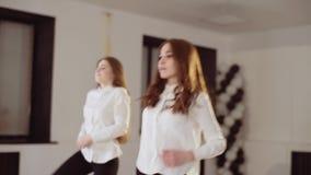 Dos chicas jóvenes están bailando en el estudio de la danza Igualación de ensayo de la danza almacen de video