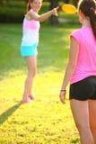 Dos chicas jóvenes están lanzando un disco volador Foto de archivo libre de regalías