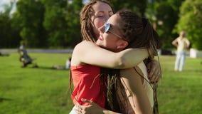 Dos chicas jóvenes felices con temen el abrazarse Amigos femeninos emocionados que se abrazan y que ríen durante almacen de metraje de vídeo
