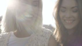 Dos chicas jóvenes felices que miran el teléfono elegante y que se divierten, al aire libre metrajes
