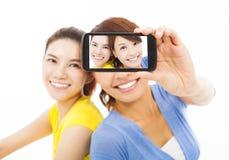 Dos chicas jóvenes felices que toman un selfie sobre blanco Foto de archivo