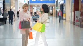 Dos chicas jóvenes felices resuelven con un abrazo en grandes almacenes mientras que hacen compras almacen de video
