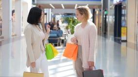 Dos chicas jóvenes felices resuelven con un abrazo en grandes almacenes mientras que hacen compras Cámara lenta almacen de video