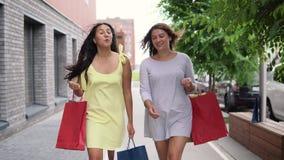 Dos chicas jóvenes hermosas caminan abajo de la calle con los bolsos en sus manos después de hacer compras, teniendo un buen humo metrajes