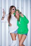 Dos chicas jóvenes hermosas con los lollipops rojos cerca de la pared Imagen de archivo
