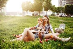 Dos chicas jóvenes hermosas en comida campestre Fotografía de archivo