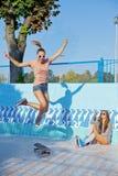 Dos chicas jóvenes hermosas en gafas de sol en una piscina vacía Fotografía de archivo