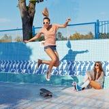 Dos chicas jóvenes hermosas en gafas de sol en una piscina vacía Imagenes de archivo