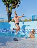 Dos chicas jóvenes hermosas en gafas de sol en una piscina vacía Imagen de archivo