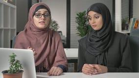 Dos chicas jóvenes hermosas en hijabs se sientan en la oficina y discuten los horario, negocio, diálogo, conversación 60 fps almacen de metraje de vídeo