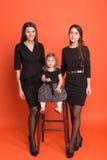 Dos chicas jóvenes hermosas en trajes de negocios y una niña adentro Imagen de archivo libre de regalías